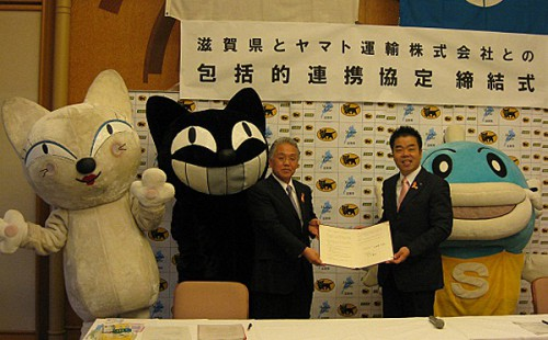左からヤマト運輸のキャラクター「シロネコ、クロネコ」、大井支社長、滋賀県三日月県知事、ご当地キャラクターの「キャッフィー」