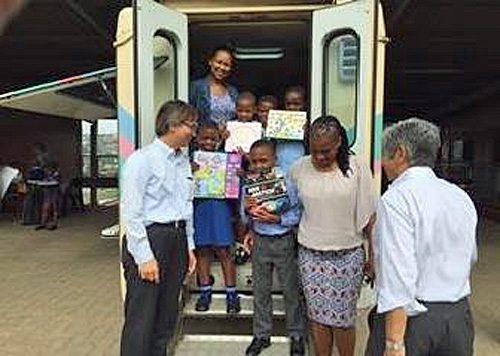 図書を抱え、喜ぶ南アフリカの子どもたち