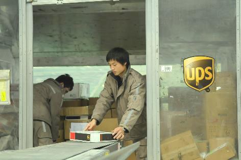 中国・上海で航空貨物コンテナに輸出貨物を積載するUPSスタッフ