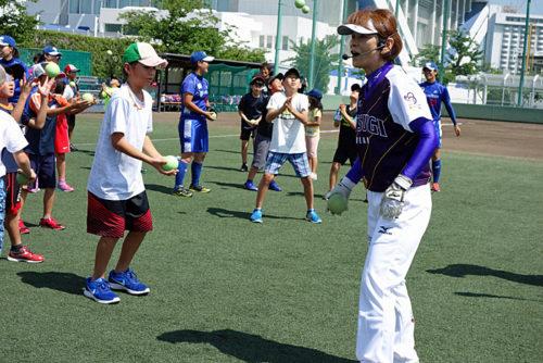 ソフトボールで宇津木妙子さんに指導を受ける子供たち