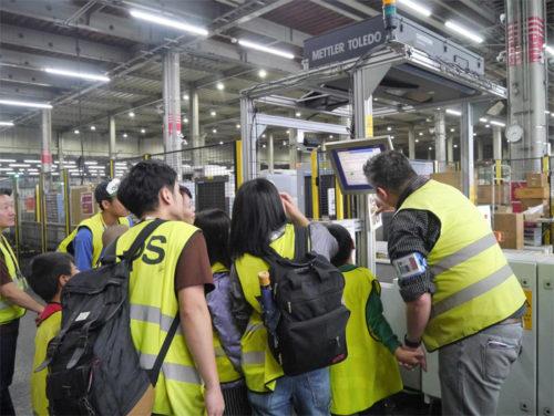 関西国際空港内の UPS ハブ施設でUPS社員にDWSシステムの説明を受ける「こどもの里」の子ども達
