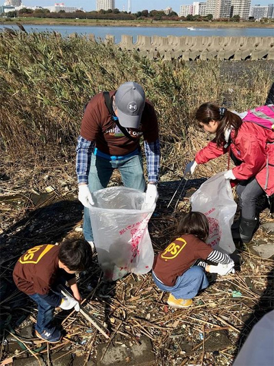 NPO法人「荒川クリーンエイド・フォーラム」主催の「トビハゼ救援クリーンエイド」で荒川のゴミ拾いをするUPS社員と家族