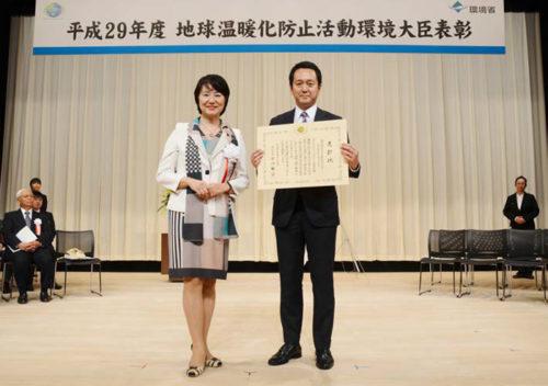 とかしきなおみ環境副大臣(左)より表彰状を授与された帖佐社長