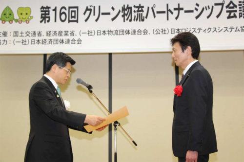 表彰状を受け取る吉岡執行役員(右)