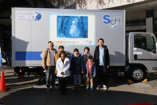 作品をラッピングしたトラック、受賞者と家族
