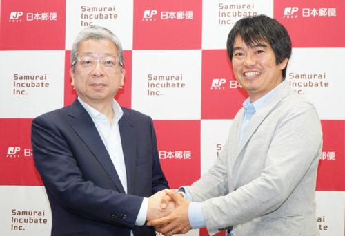 握手する日本郵便の横山社長(左)とサムライインキュベートの榊原代表取締役(右)