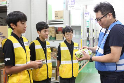 商品保管室で商品について説明を受ける中学生