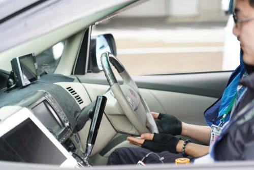 自動走行車両の運転席。ドライバーはハンドルに手を添えているだけ