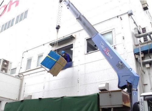 トラック車両に取り付けられた器具と複合機を固定する作業。輸送中の荷崩れを防止する