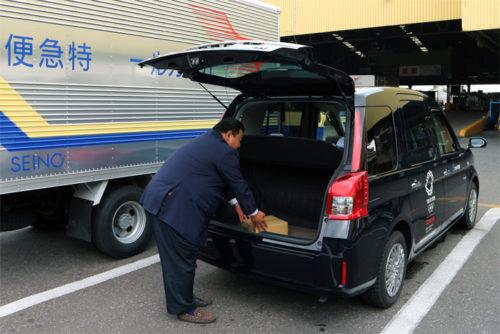荷物をタクシーのトランクに入れる