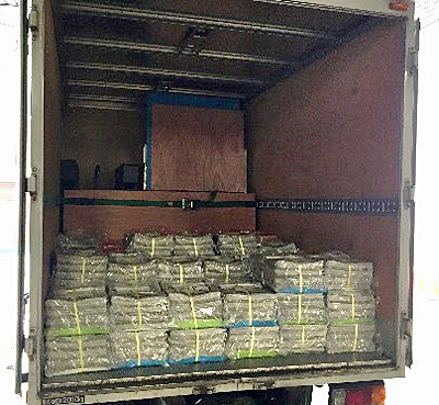 奥に段ボールで梱包された食塩、手前に読売新聞が積まれたトラック荷台