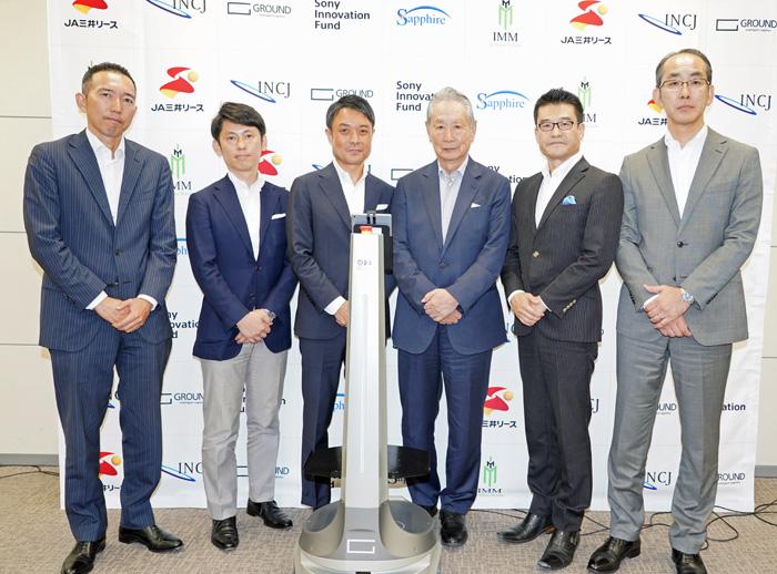 出資企業のそれぞれの代表と宮田社長、前方の機器はAMR