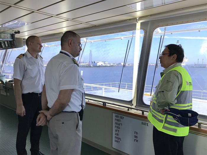 自動車専用船「HERITAGE LEADER」のブリッジで船長らと意見交換する長澤仁志社長(右)