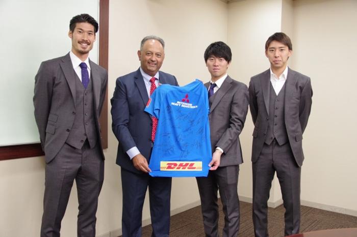 DHLのオフィスを表敬訪問し、サイン入りウエアをプレゼントする浦和レッズの選手たち。 (左から鈴木大輔選手、 DHLジャパン トニー カーン社長、武藤雄樹選手、柴戸海選手)