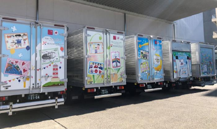 子供たちの描いた絵でラッピングされたトラック