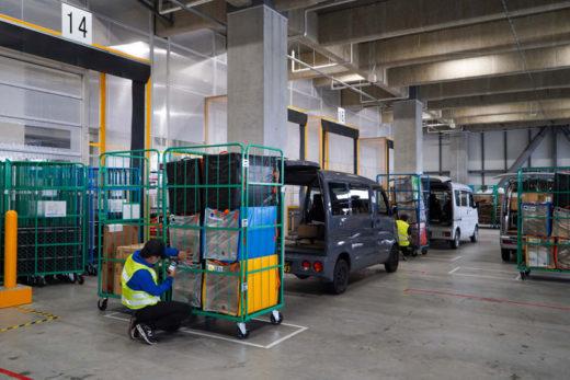 Amazon Flexドライバーがデリバリーステーションで配送商品を受け取り、荷詰めの作業