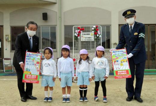 贈呈式の様子:(左)小丸成洋理事長、天使幼稚園の園児たち(中央)、福山東警察署の政近利久署長